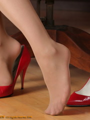 Amazing brunette secretary laying on her boss's desk only in beads and her red high heels