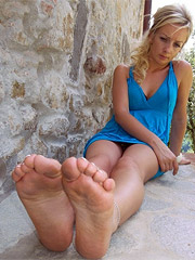 Delicious petite blonde babe in blue dress exposing pretty feet outdoors.