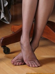 Long-haired brunette in a grey dress and black stockings undresses to show off her shaggy cooch in her office