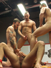 Four nude male studs wrestle before audience and losers get to suck winner's cocks