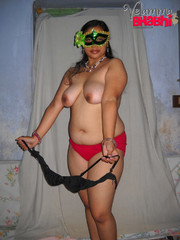 Plumper indian bitch in a mask takes off her sari, bra and red panties to pose naked