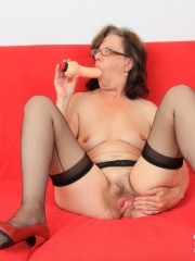 Matured chick in glasses shows hairy matured pussy, sucks dildo and puts in pussy
