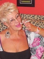 Gorgeous copper colored hair granny unleashes her seductive poses showing her firm tits and pink pussy