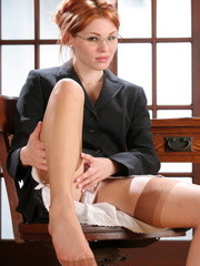 Nasty ginger babe in glasses taking off her secretary's suit to pose topless in stockings in her office