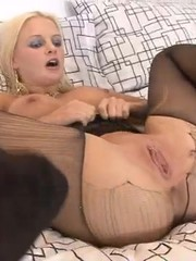 Cock craving blonde babe in awesome stay ups pleasing her wet snatch on the leather sofa.