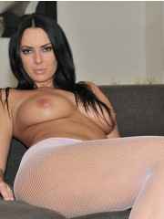 Busty brunette beauty demonstrating her big tits laying on the sofa in fishnet tights